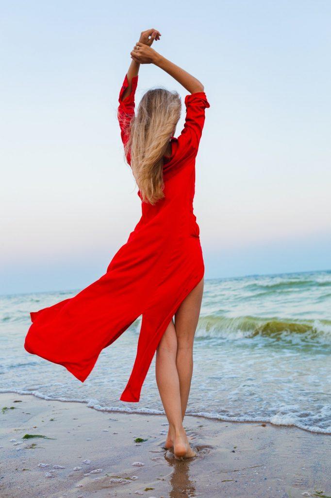 beautiful free woman in red dress in wind on sea beach